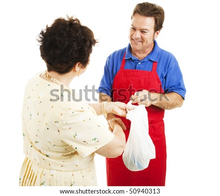 Friendly shop man hands a woman her purchases in a bag.  Isolated on white. - stock photo