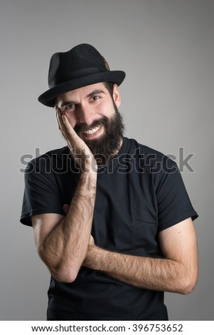 Friendly smiling bearded hipster wearing black t-shirt and hat with head resting on his hand.  Headshot portrait over gray studio background with vignette.