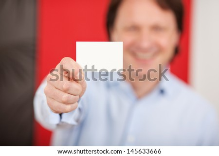 friendly smiling man in a shop showing white card - stock photo