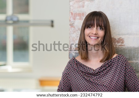 Friendly smiling woman in a trendy top leaning on a grunge wall indoors looking at the camera, close up head and shoulders with copyspace - stock photo