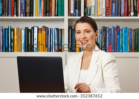 Friendly smiling woman in front of a computer in a library, consultant, counselor, adviser, customer service, online helpdesk - stock photo