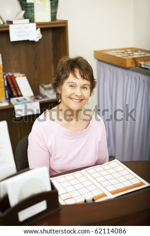 Friendly store clerk or secretary sitting behind her desk. - stock photo