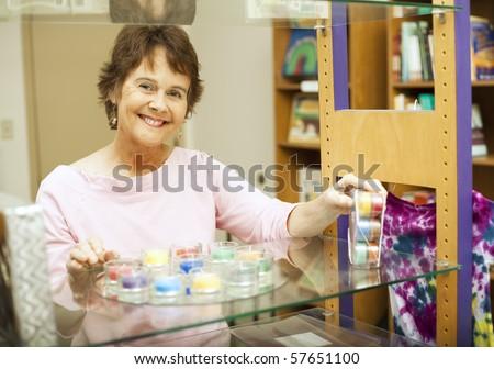 Friendly store clerk smiles as she's setting up a display.
