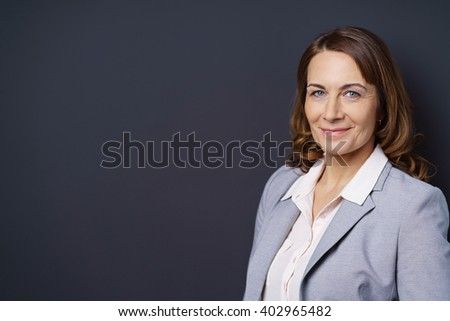 Friendly stylish confident middle-aged businesswoman or manageress standing at and angle turning to smile at the camera, with copy space - stock photo