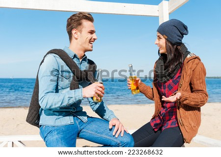 Friendly talk. Handsome young man and woman talking to each other and smiling while drinking beer on the beach  - stock photo