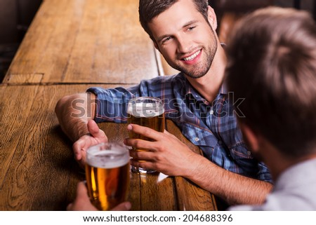 Friendly talk in bar. Top view of two happy young men talking to each other and gesturing while drinking beer at the bar counter  - stock photo