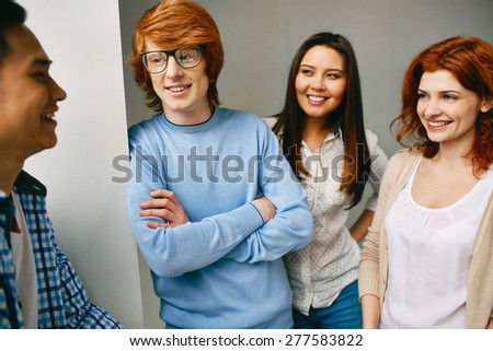 Friendly teenage students talking during break - stock photo
