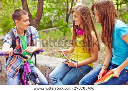 Friendly teenagers communicating in natural environment - stock photo
