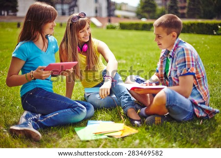 Friendly teenagers resting on green lawn in park - stock photo