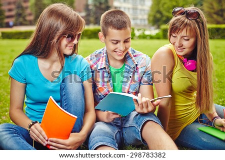 Friendly teenagers with exercise-books carrying college tasks on green lawn - stock photo