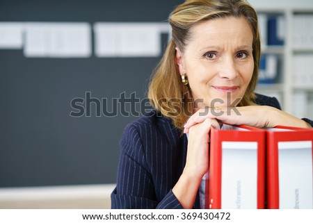 Friendly thoughtful middle-aged businesswoman resting her chin on office binders smiling at the camera, close up view with copy space