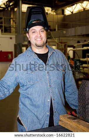 Friendly welder on the floor of a factory.  Authentic and accurate content depiction. - stock photo