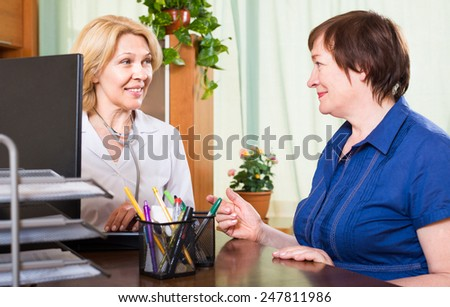 Friendly woman doctor sitting next to a smiling patient and talking - stock photo