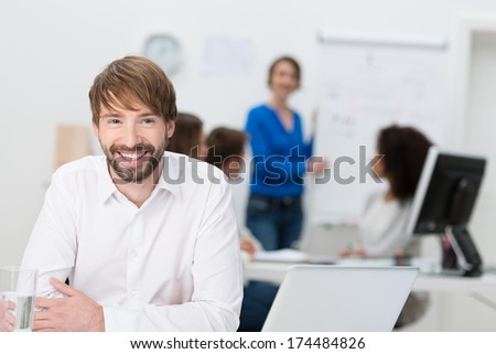 Friendly young businessman sitting at his desk in the office relaxing as he smiles at the camera with his colleagues at work behind him - stock photo
