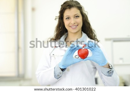 Friendly young female doctor holding a heart in his hands
