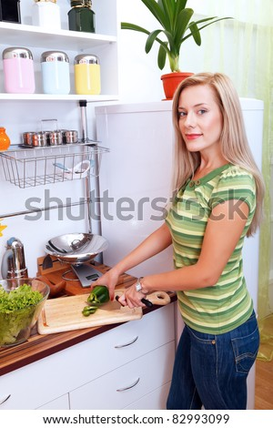 Friendly young woman cooking a meal - stock photo
