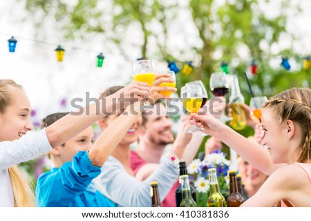 Friends and neighbors toasting on garden party - stock photo