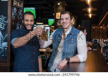Friends are having fun with beer. Portrait of two handsome friends in a pub with glasses of beer
