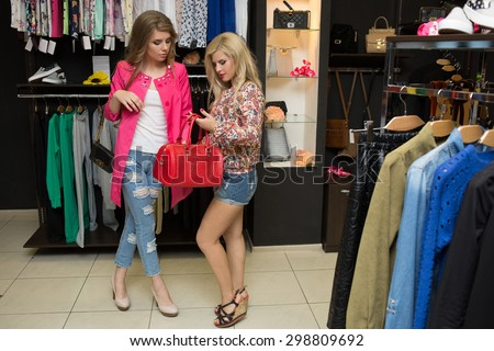 Friends are seeking for a dress at the clothes shop - stock photo