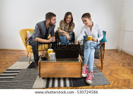 Friends at a coffee break talking and looking in to a laptop