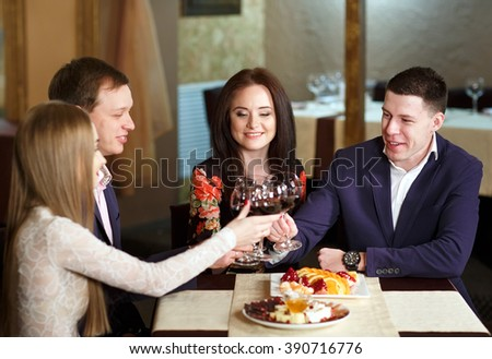 Friends at a restaurant drinking wine. - stock photo