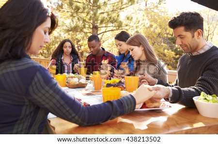 Friends at a table at a barbecue saying grace before eating - stock photo
