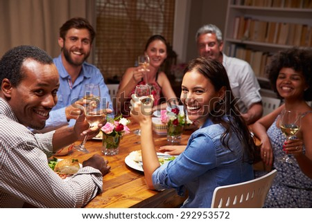 Friends at an evening dinner party, looking at camera - stock photo
