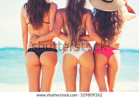 Friends at the Beach. Beautiful girls on sunny tropical beach in bikinis - stock photo