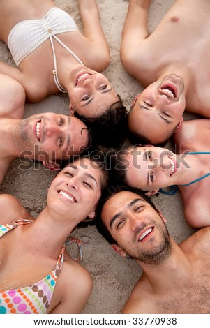 Friends at the beach with their heads together on the floor