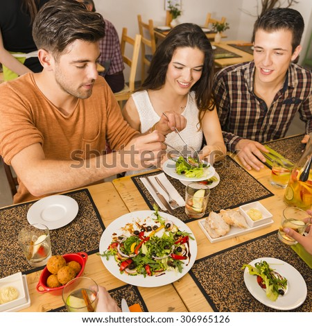 Friends at the restaurant and being served of food in the plate - stock photo