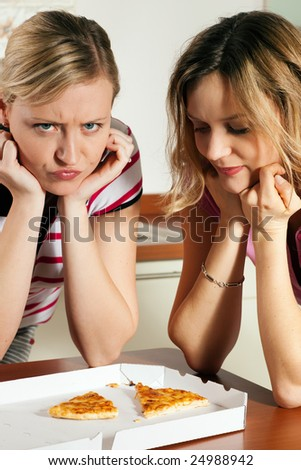 Friends being fed up of pizza wishing they had cooked themselves - stock photo