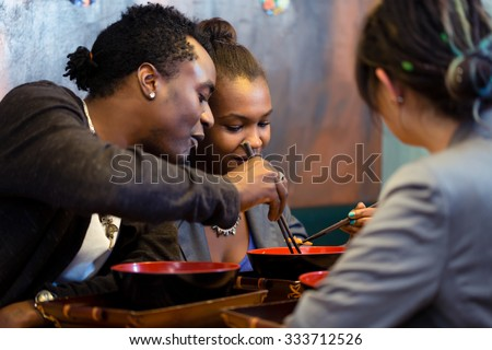 Friends, black and Latin people, eating ramen noodle soup in Japanese Restaurant - stock photo