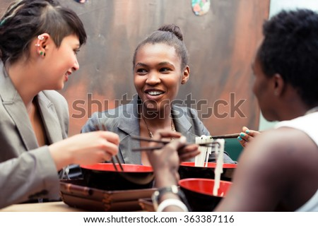 Friends, black and Latin people, eating ramen noodle soup in Japanese Restaurant