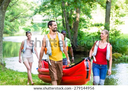 Friends carrying kayak or canoe to forest river - stock photo