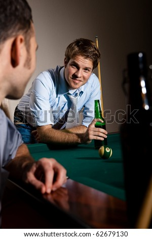 Friends chatting at snooker table, having beer, smiling.? - stock photo