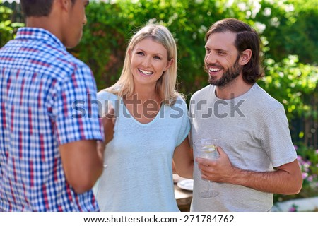 friends chatting outdoors at garden party gathering with cocktail wine drinks - stock photo