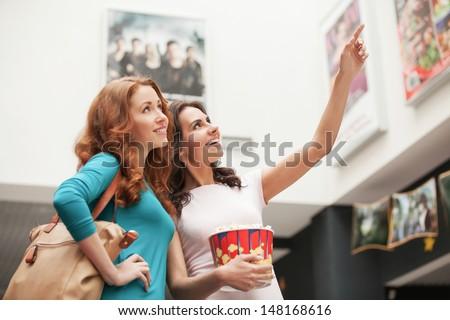 Friends choosing movie at the cinema. Beautiful young female friends choosing movie to see at the cinema - stock photo