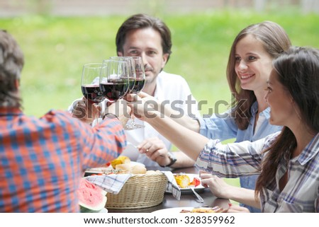 Friends clink glasses of red wine at outdoor dinner - stock photo