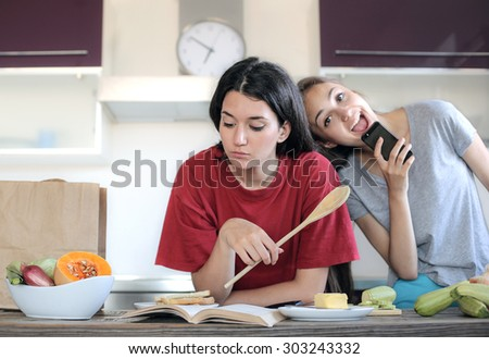 Friends cooking in the kitchen - stock photo