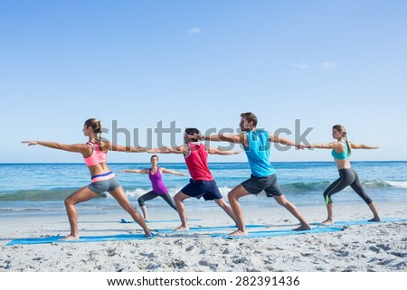 Friends doing yoga together with their teacher at the beach - stock photo