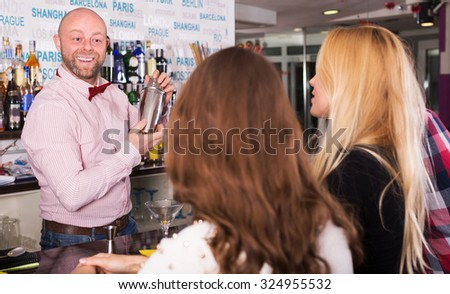 Friends drinking and chatting with happy barman at bar counter - stock photo