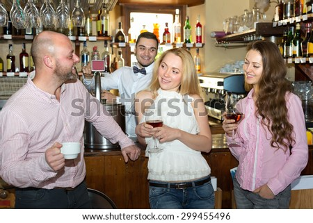 Friends drinking and chatting with smiling barman at bar counter - stock photo