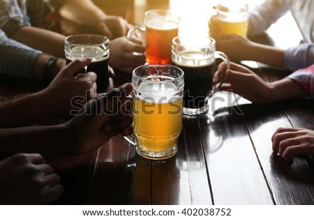Friends drinking beer in pub - stock photo