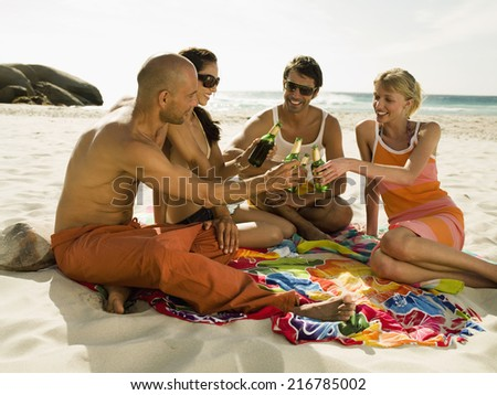Friends drinking beer on the beach. - stock photo