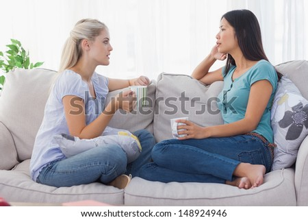 Friends drinking coffee and having a serious chat at home on the couch - stock photo