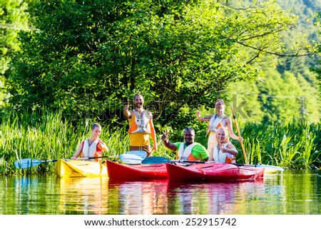 Friends driving with kayak on forest river - stock photo