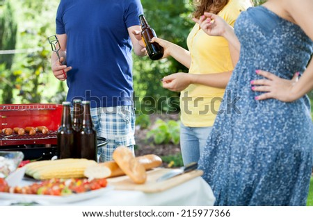 Friends during barbecue in a garden, horizontal - stock photo