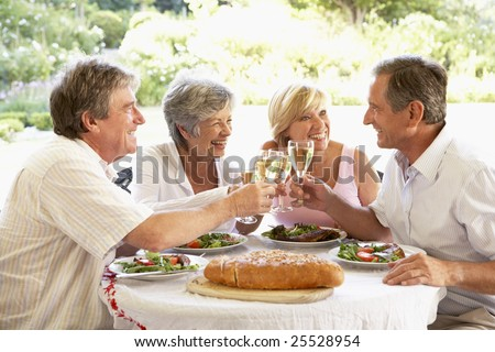 Friends Eating An Al Fresco Lunch, Holding Wineglasses - stock photo