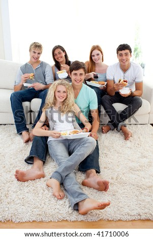 Friends eating burgers and fries on the sofa - stock photo