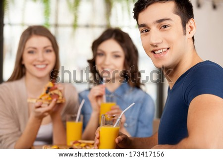 Friends eating pizza. Three cheerful young people eating pizza at the restaurant while man looking over shoulder and smiling at camera - stock photo